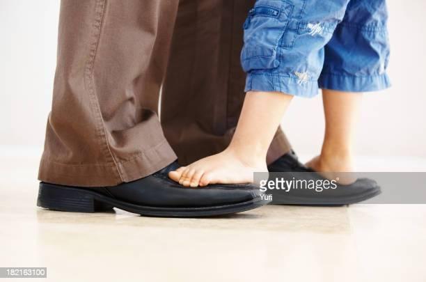 Pai carregar filho em seus pés