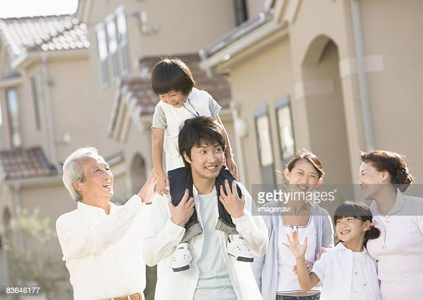 Father carrying son on his shoulders and his family
