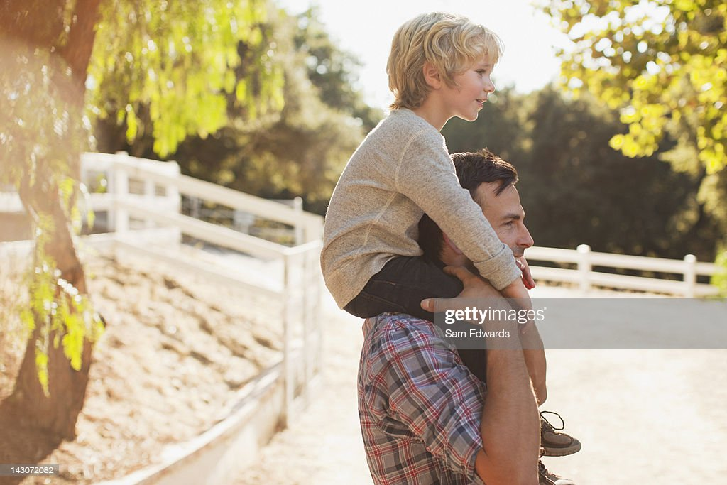 Father carrying son on his shoulders : Stock Photo