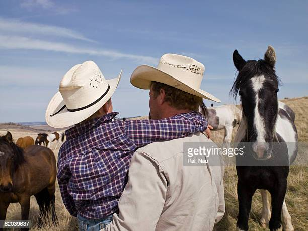 Father carrying son on horse ranch