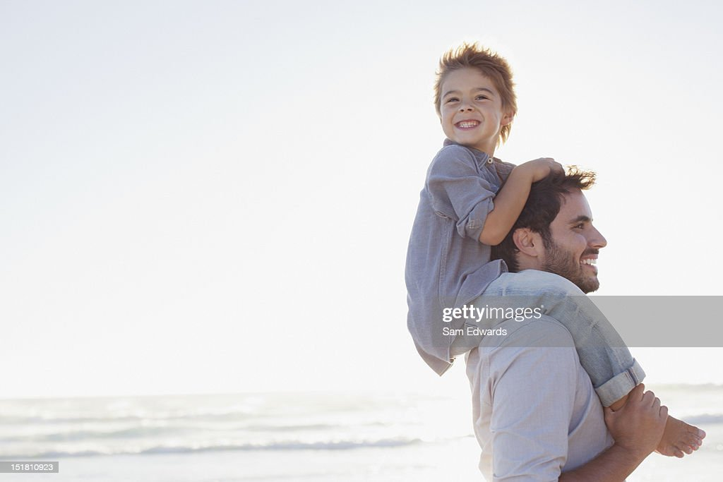 Father carrying son on shoulders on beach : Stock Photo