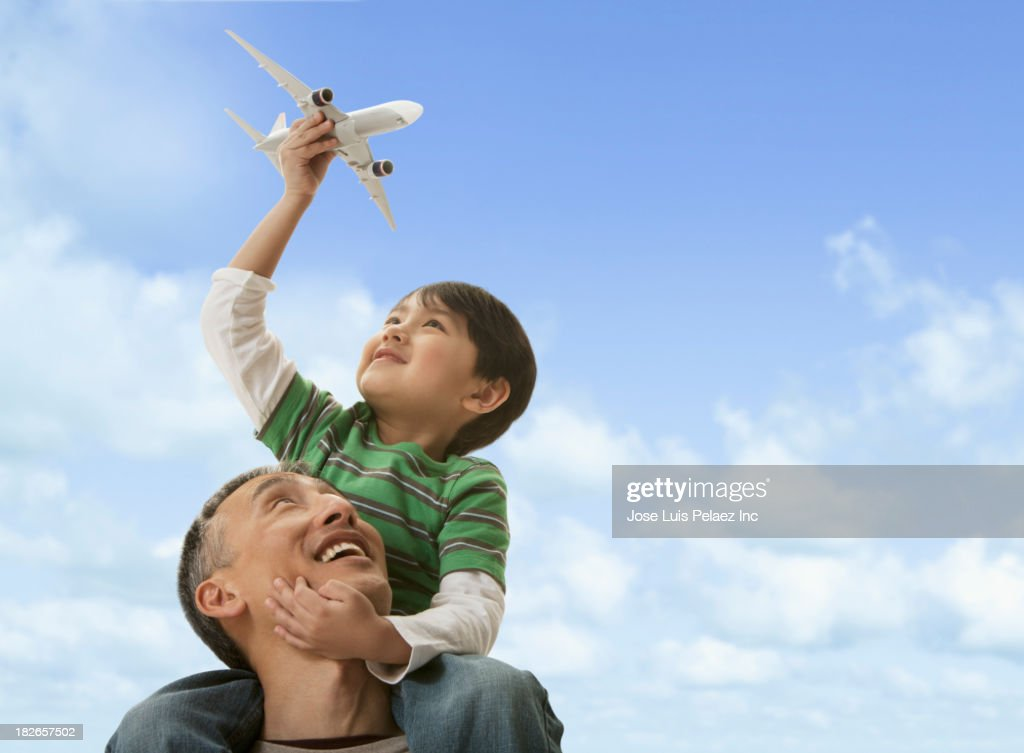 Father carrying son on shoulders outdoors : Stock Photo