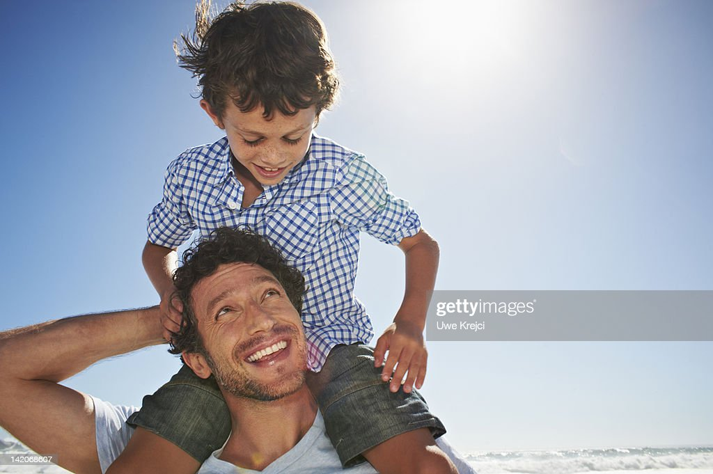 Father carrying son on shoulders : Stock Photo