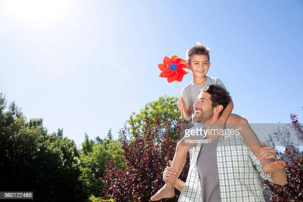 Father carrying son on shoulders, playing in garden