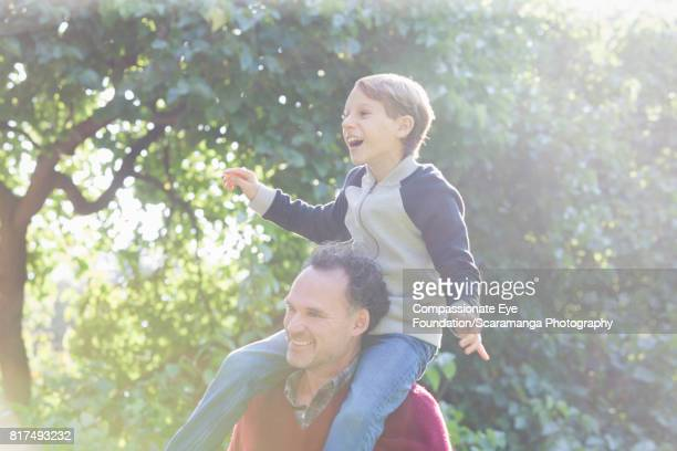 Father carrying son piggyback in backyard