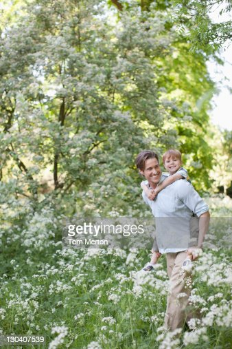 Father carrying son piggyback in park : Stock Photo