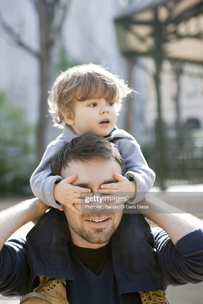 Father carrying toddler son on his shoulders, son covering father's eyes with his hands : Stock Photo