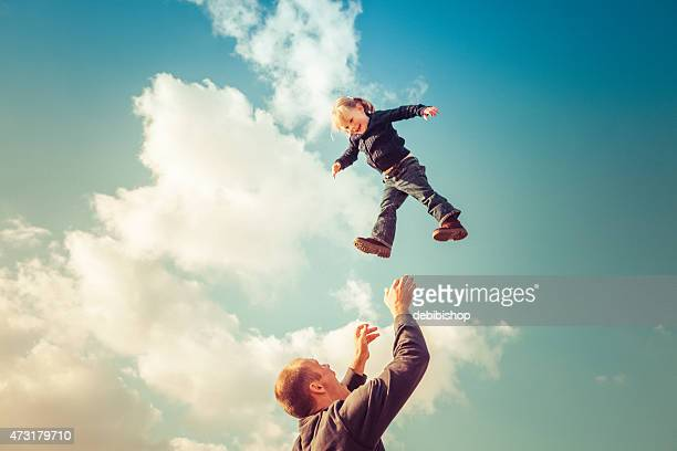 Father catching girl falling from cloudy sky