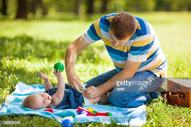 Father Changing Baby Diaper Outdoors.