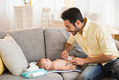 Father changing baby's diaper on sofa