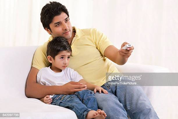 Father changing channels while sitting with his son
