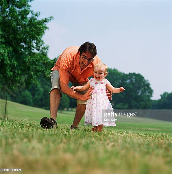 Father Chasing Baby in Park