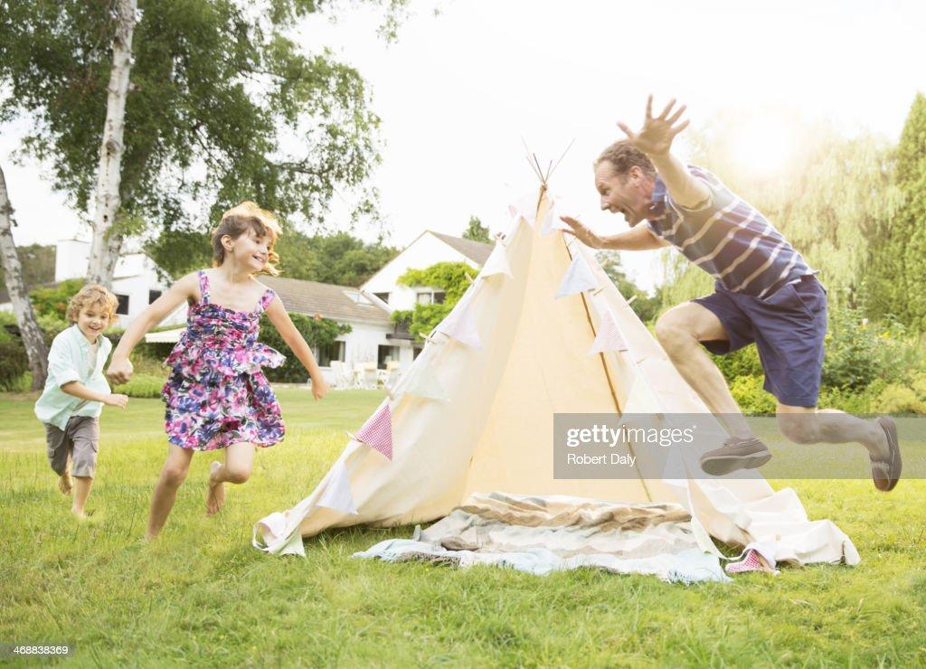 Father chasing children around teepee in backyard : Stock Photo