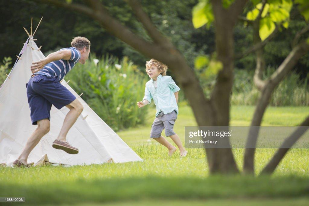 Father chasing son around teepee in backyard