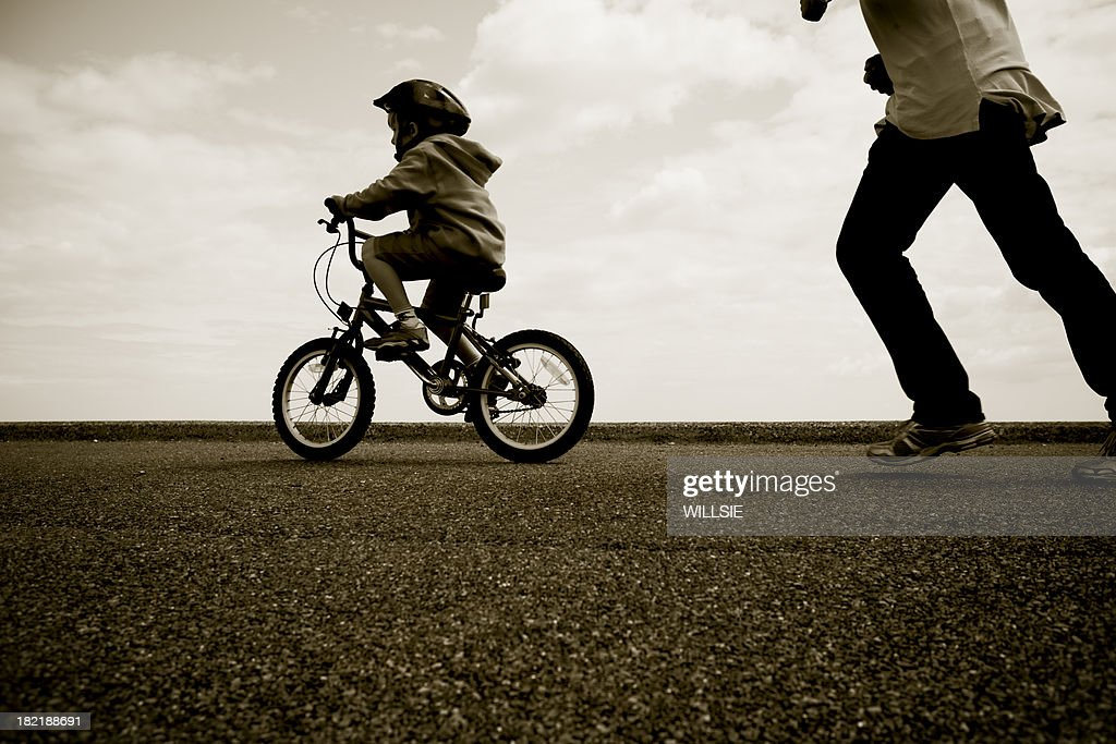 Father chasing young cyclist learning to ride