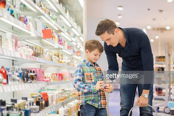 Father choosing perfume with son