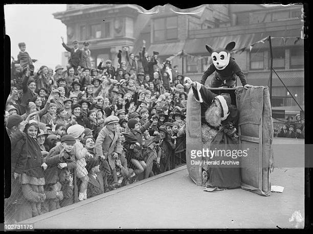 Father Christmas arrives at Selfridges by parcel post with Mickey Mouse 1935 A crowd of children watches as Father Christmas emerges from a giant...