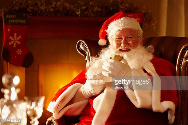 Father Christmas enjoying a mince pie by the fire