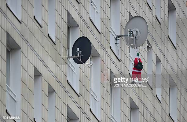 A Father Christmas figure dangles from a satellite dish fixed on a high rise building in Berlin on December 15 2015 / AFP / JOHN MacDOUGALL
