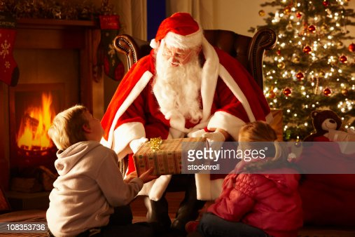 Father Christmas giving gift to children in grotto