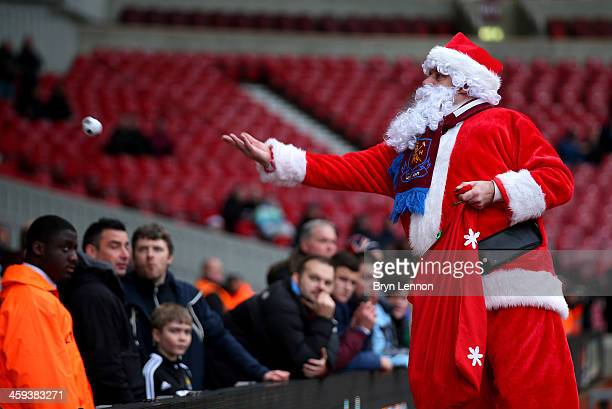 'Father Christmas' greets fans prior to the Barclays Premier League match between West Ham United and Arsenal at Boleyn Ground on December 26 2013 in...