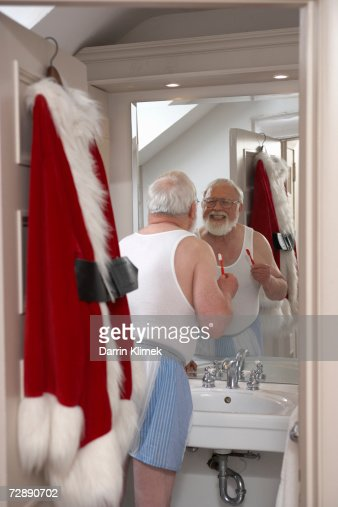Father Christmas in bathroom, cleaning teeth : Stock Photo
