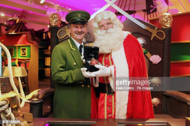 Father Christmas poses with a Harrods Greenman and a one off bauble with a 15000 price tag on sale in Harrods Christmas World which opened today
