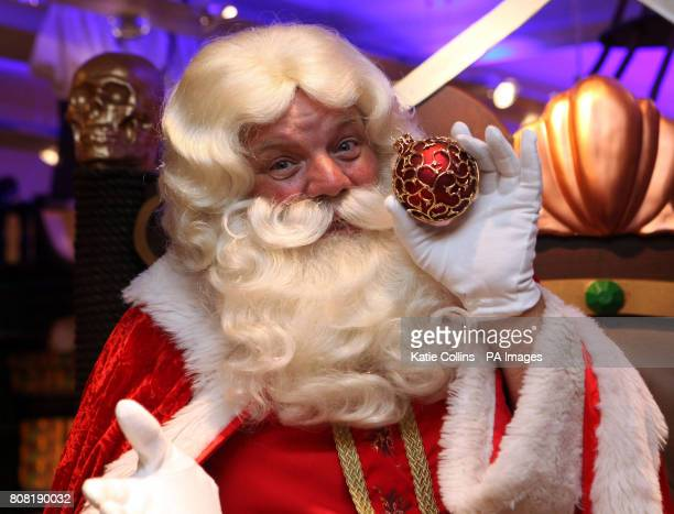 Father Christmas poses with a one off bauble with a 15000 price tag on sale in Harrods Christmas World which opened today