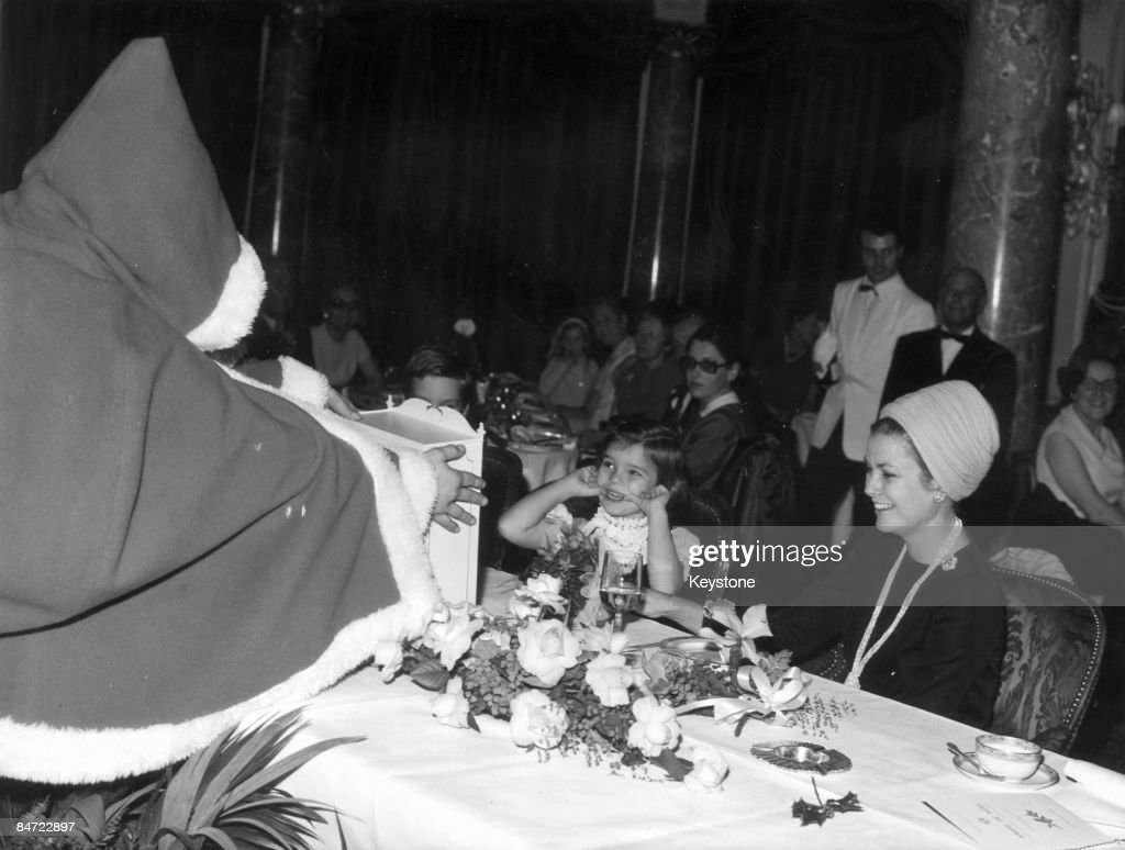 Father Christmas presents Princess Stephanie of Monaco with a seasonal gift during the Christmas Tree Festival for children of police officers in Monaco, 23rd December 1969. Next to Stephanie is her mother, Princess Grace (1929 - 1982).