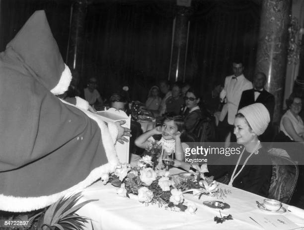 Father Christmas presents Princess Stephanie of Monaco with a seasonal gift during the Christmas Tree Festival for children of police officers in...