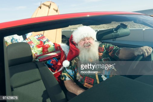 Father Christmas sits in red convertible with surfboard : Foto stock