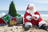 Father Christmas sits on the beach with a tree and presents