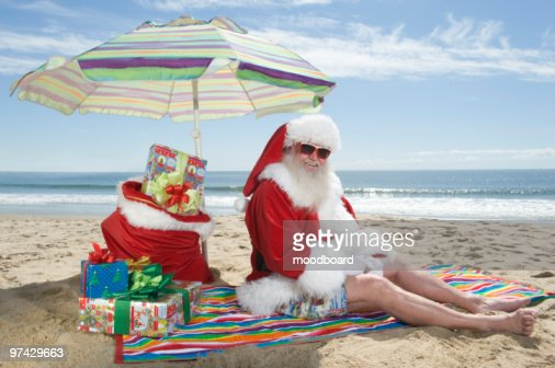 Father Christmas sits under a parasol on the beach : Stock-Foto