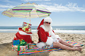 Father Christmas sits under a parasol on the beach