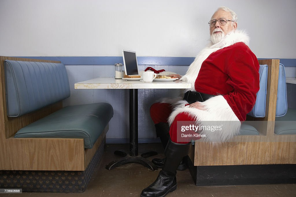 Father Christmas sitting in booth at diner, having breakfast : Stock Photo