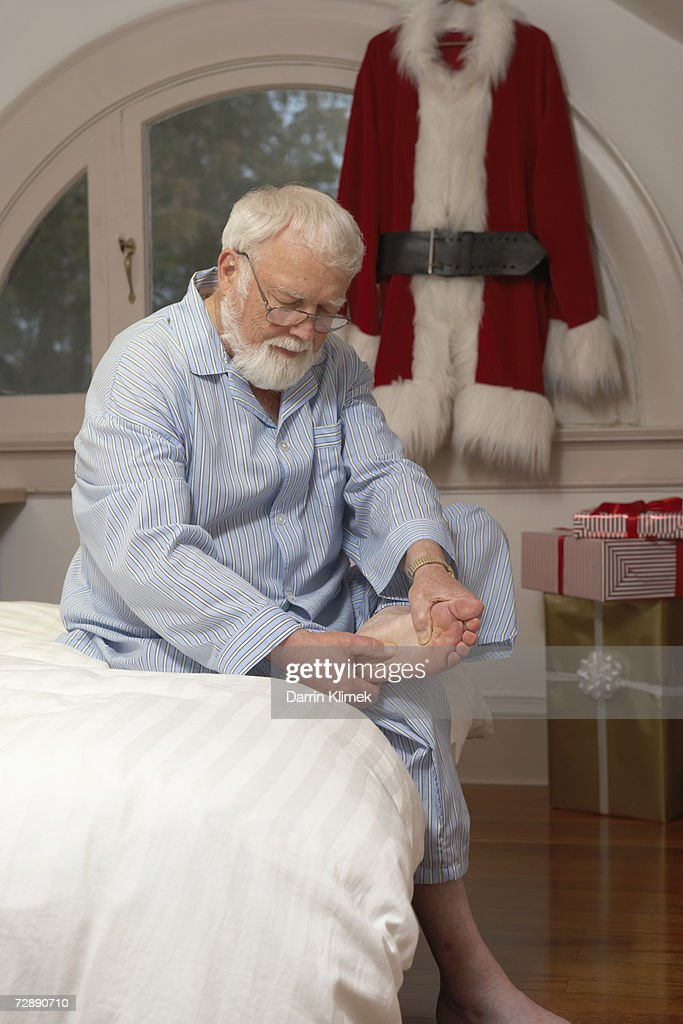 Father Christmas sitting on bed, looking at foot : Stock Photo
