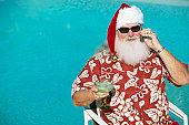 Father Christmas Wearing a Hawaiian Shirt Sitting by a Swimming Pool Holding a Mobile Phone and a Cocktail Glass