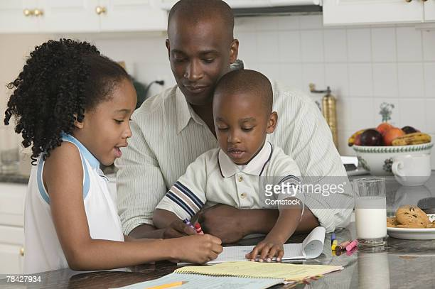 Father coloring with children in kitchen