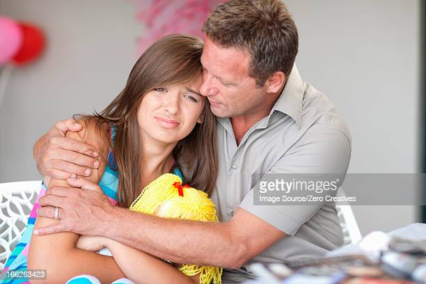Father comforting teenage daughter