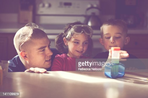 Father conducting science experiment with his kids