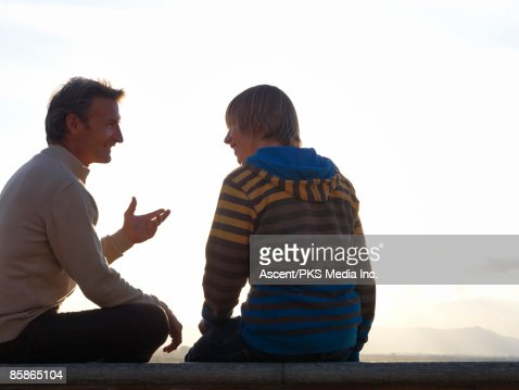 Father converses with son on top of wall, mtns  : Stock Photo