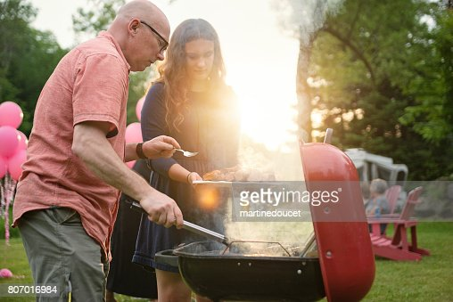 Father cooking meat on barbecue, at big family gathering summer outdoors. : Stock Photo