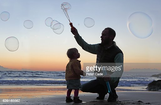 Father creating bubbles on beach with toddler
