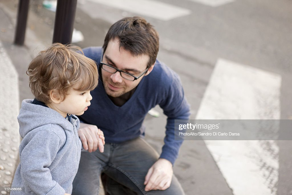 Father crouching beside toddler son, holding his hand : Stock Photo