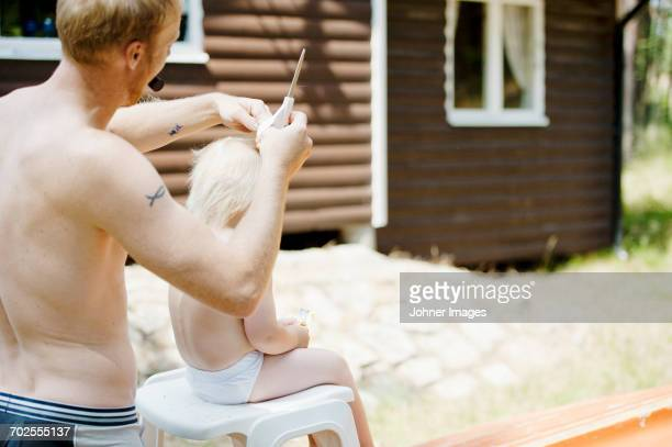 Father cutting hair of son outdoors