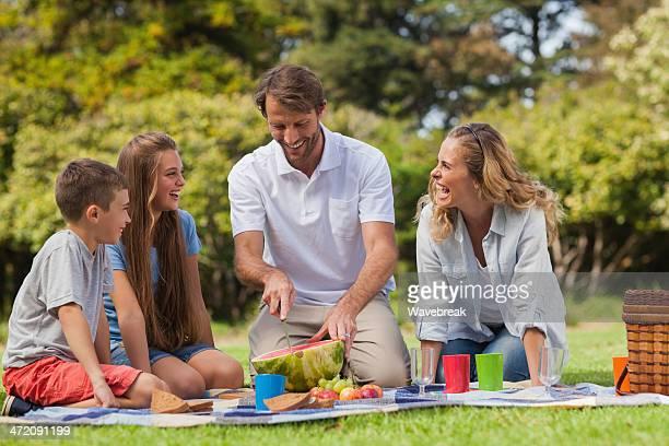 Père couper pastèque tandis que sa famille rire