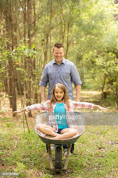 Father, daughter clean-up yard. Family garden outdoors. Wheelbarrow fun.
