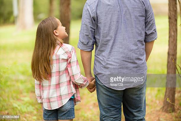 Father, daughter hold hands outdoors. Parent, child. Love, affection.