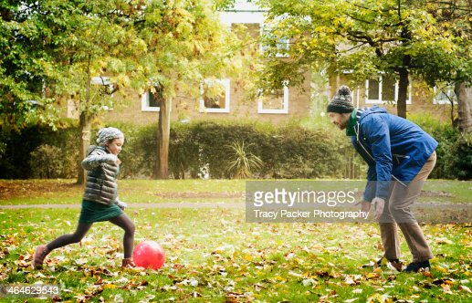 Father & daughter play football in a London park