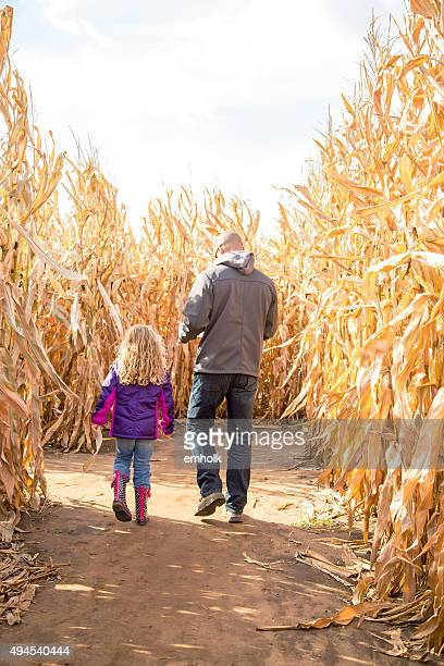 Father & Daughter Walking Through Autumn Corn Maze